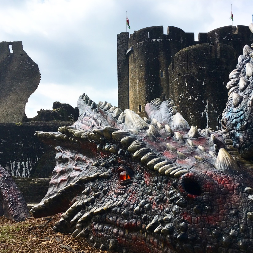 A large dragon's head with Caerphilly Castle in the background