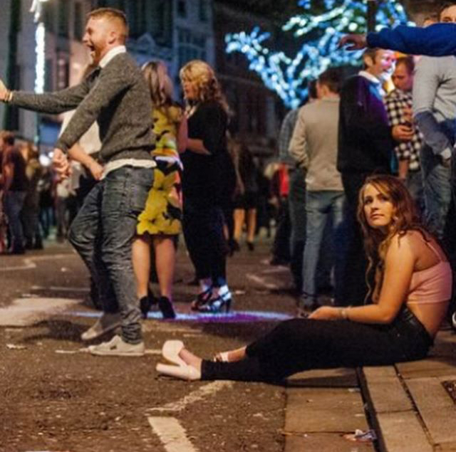 Christmas revellers on the streets, Christmas lights in the background, a man dancing in the road and a woman sits on the curb.