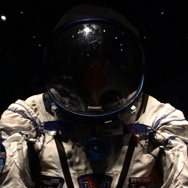 Tim Peake's spacesuit and helmet on display at National Museum Cardiff. the light bounces off the top of the glass helmet and the dark background make it look like it's in space.