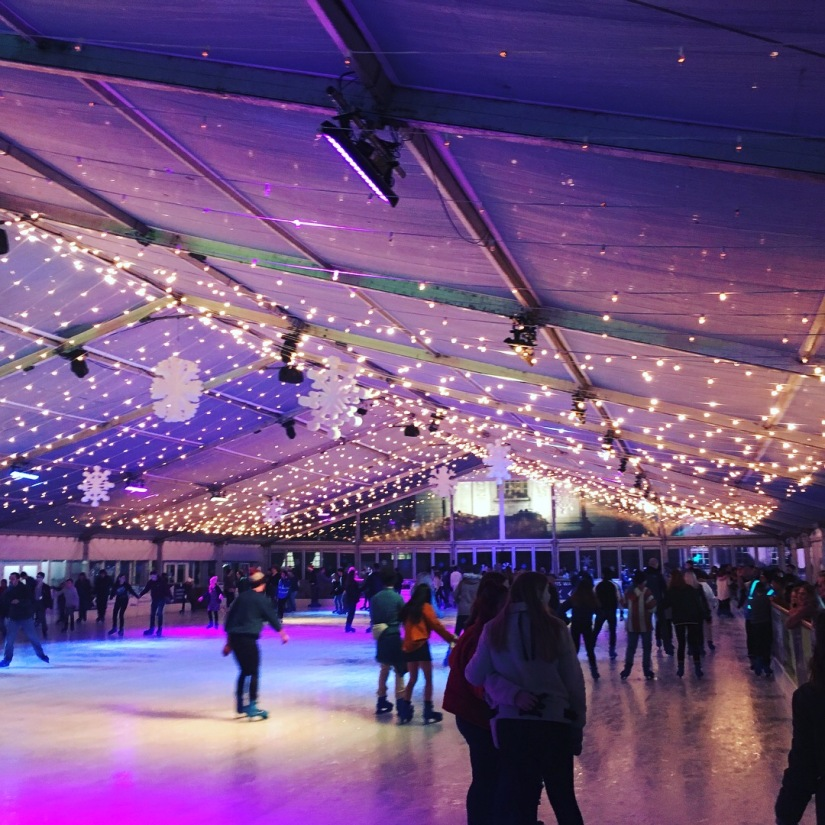 An ice skating rink with fairy lights on the ceiling.