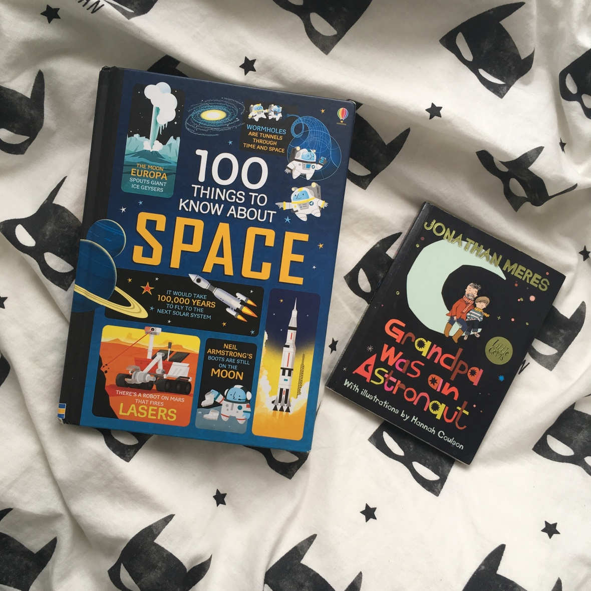 Two children's books on batman bedding. The larger book on the left is 100 Things to Know About Space and the other book is Grandpa Was an Astronaut by Jonathan Meres.