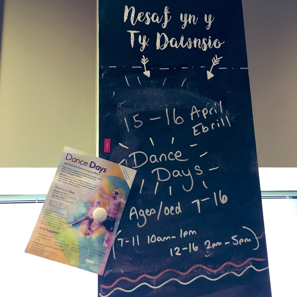 a blackboard pillar has been written on with chalk with dates and times for Dance Days. A Dance Days flyer is stuck to the pillar with a magnet.