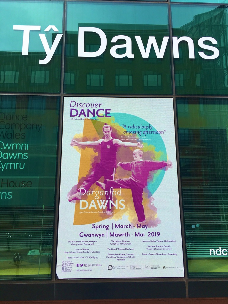 The outside of the Dance House with large printed words saying Ty Dawns and a massive Discover Dance poster showing a male dancer and a boy in school uniform copying his one legged, arms out pose.