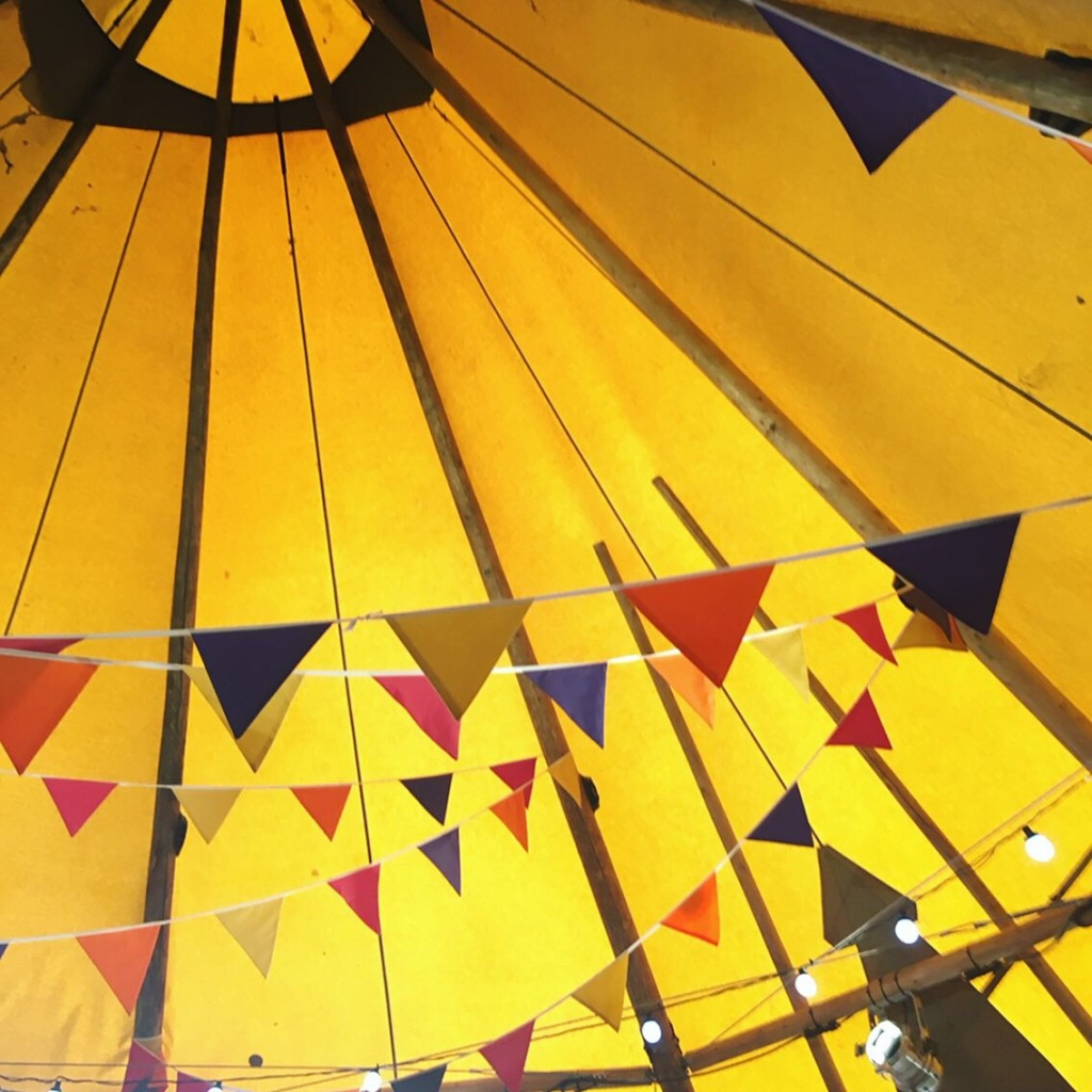 Inside the roof of a teepee style tent with bunting and garland lights.