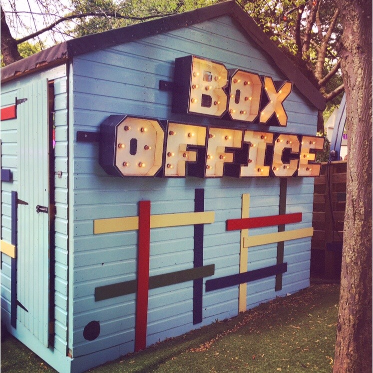 The words BOX OFFICE glow in lights on the side of a wooden shed.