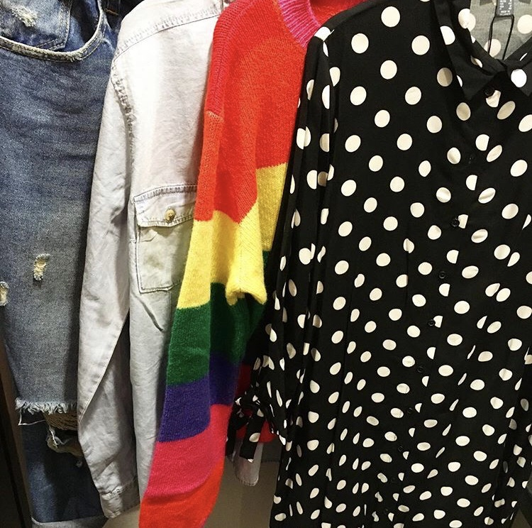 Four items of clothes hang. From letf to right: a pair of blue ripped jeans, a chambray long sleeved shirt, a rainbow woollen jumper and aspotty shirt dress.