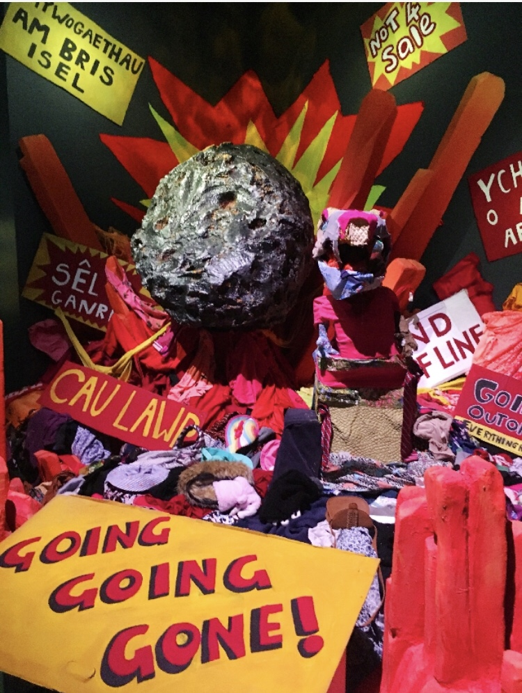 "A display at the museum of a meteor model blasting into shop sale signs reading ""Going Going Gone!"""