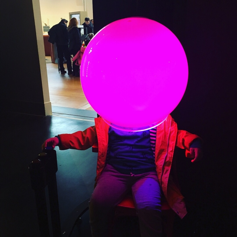 a young child sits on a chair, their head in a gint glowing orb