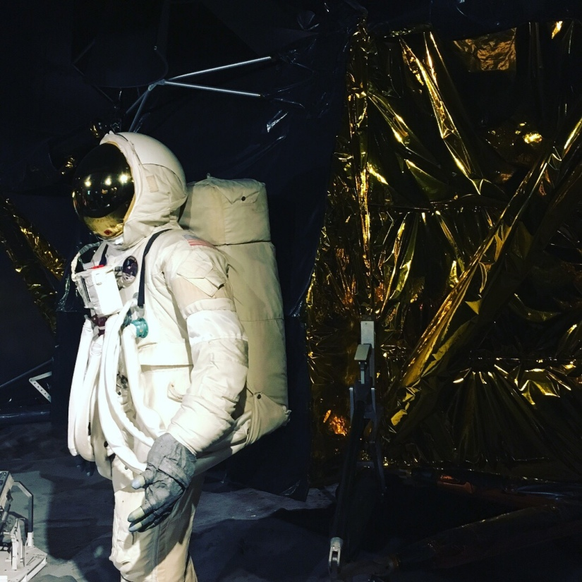 an astronaut model in the ful gear stands next to a shiny gold space thing