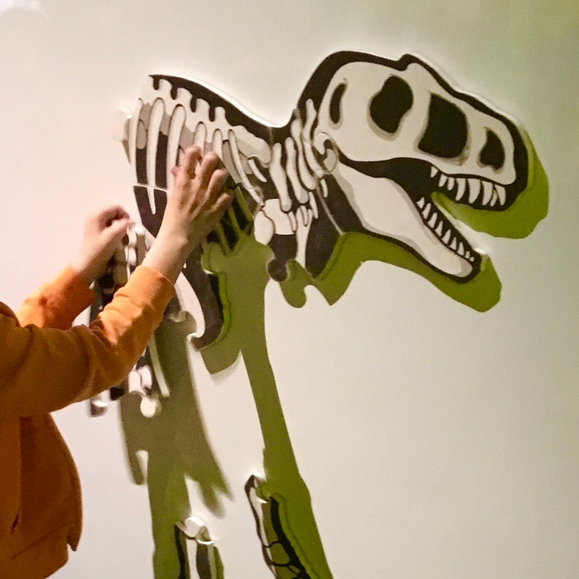 child assembles a giant magnetic dinosaur skeleton jigsaw