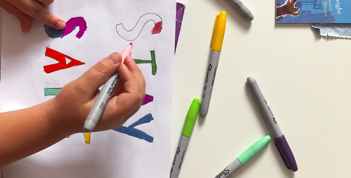 shot from above, a child's hand hols a colouring pen above a sheet that spells out STAY SAFE. Other colouring pens are scattered across the table and in the top left of the image, the corner of a picture book pokes into shot.